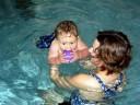 Baby im Wasser von Händen gehalten